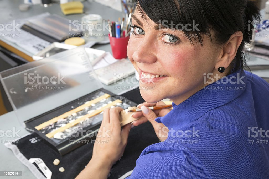 Technician in dental laboratory applying ceramics to a prosthesis royalty-free stock photo