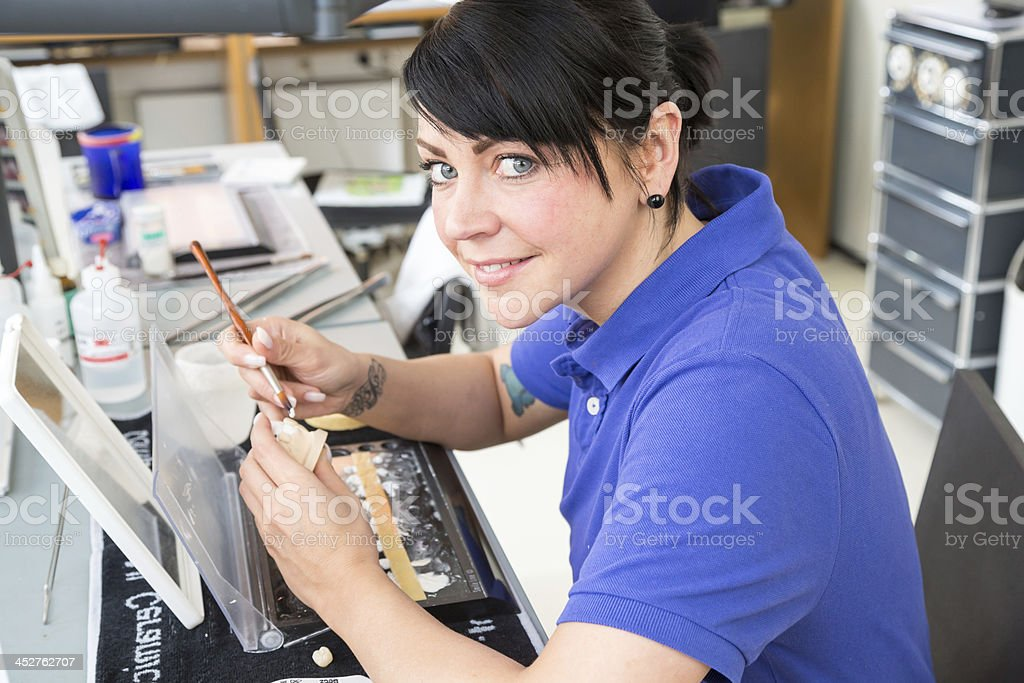 Technician in dental laboratory applying ceramics to a prosthesis stock photo