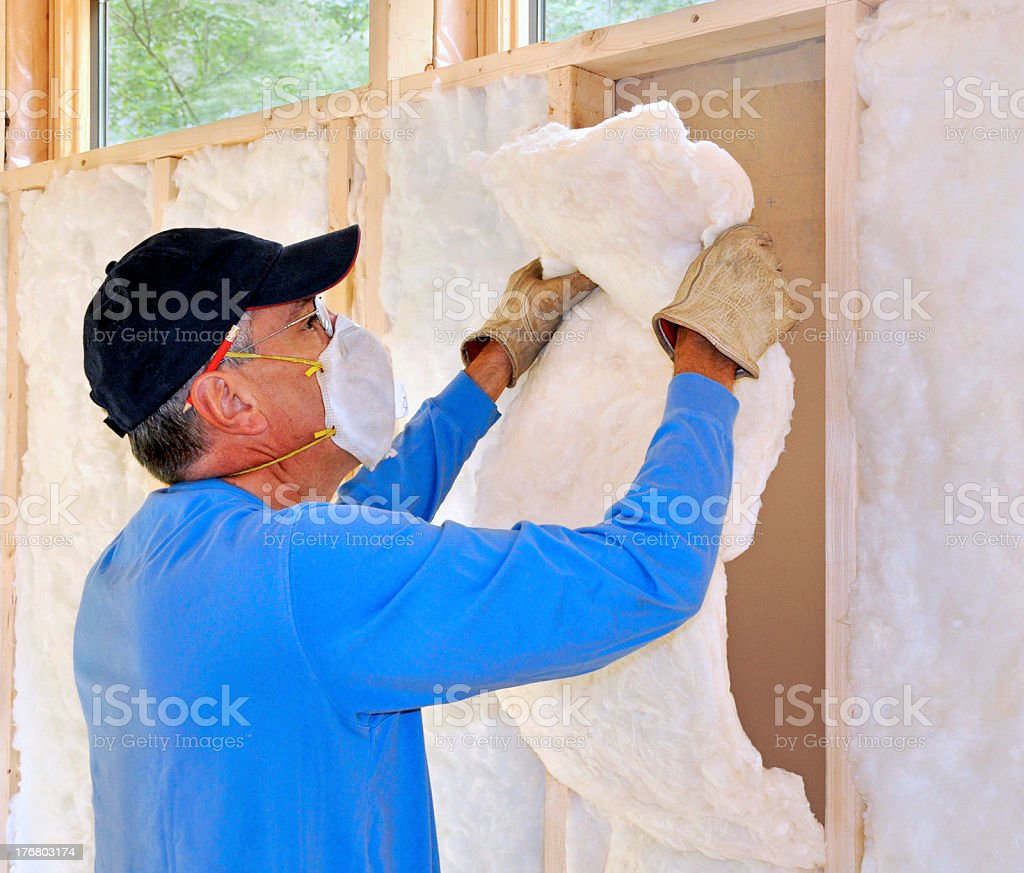 Technician in mask installing fiberglass insulation stock photo