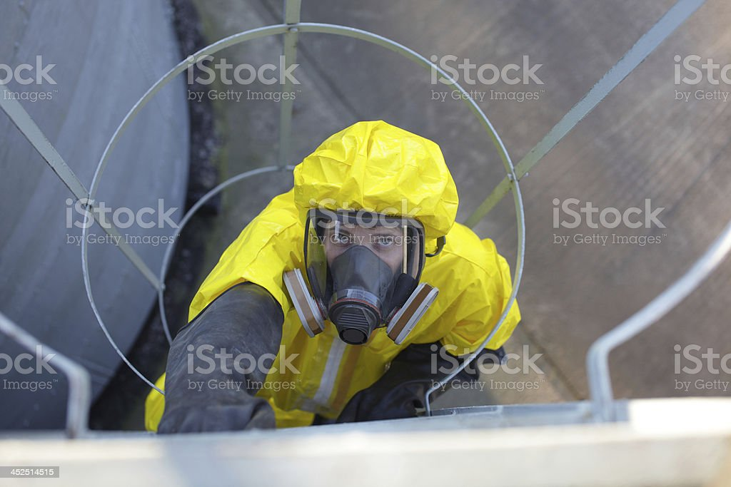 technician in protective uniform going up a metal ladder stock photo