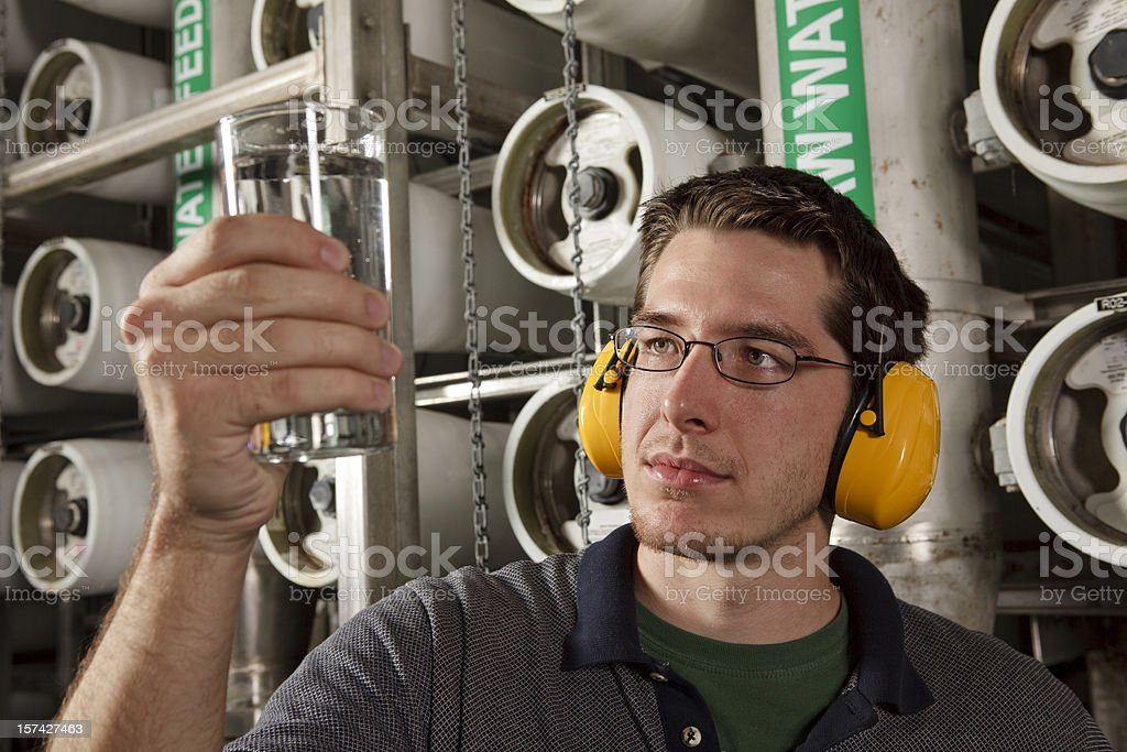 Technician in Reverse Osmosis Water Purification Plant Checks Quality stock photo