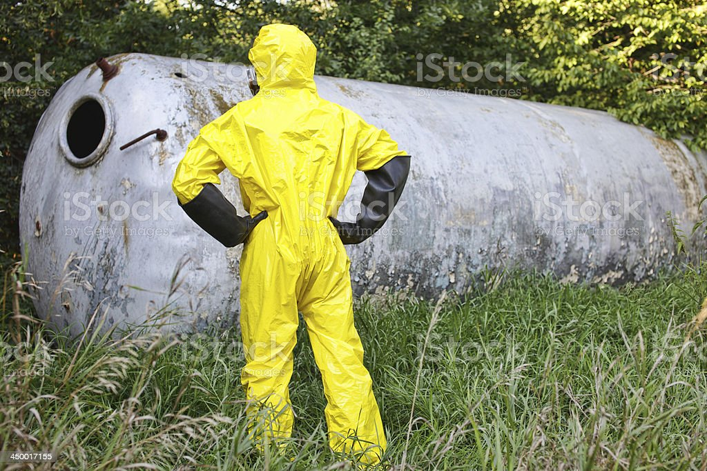 technician in uniform examining large stainless tank royalty-free stock photo