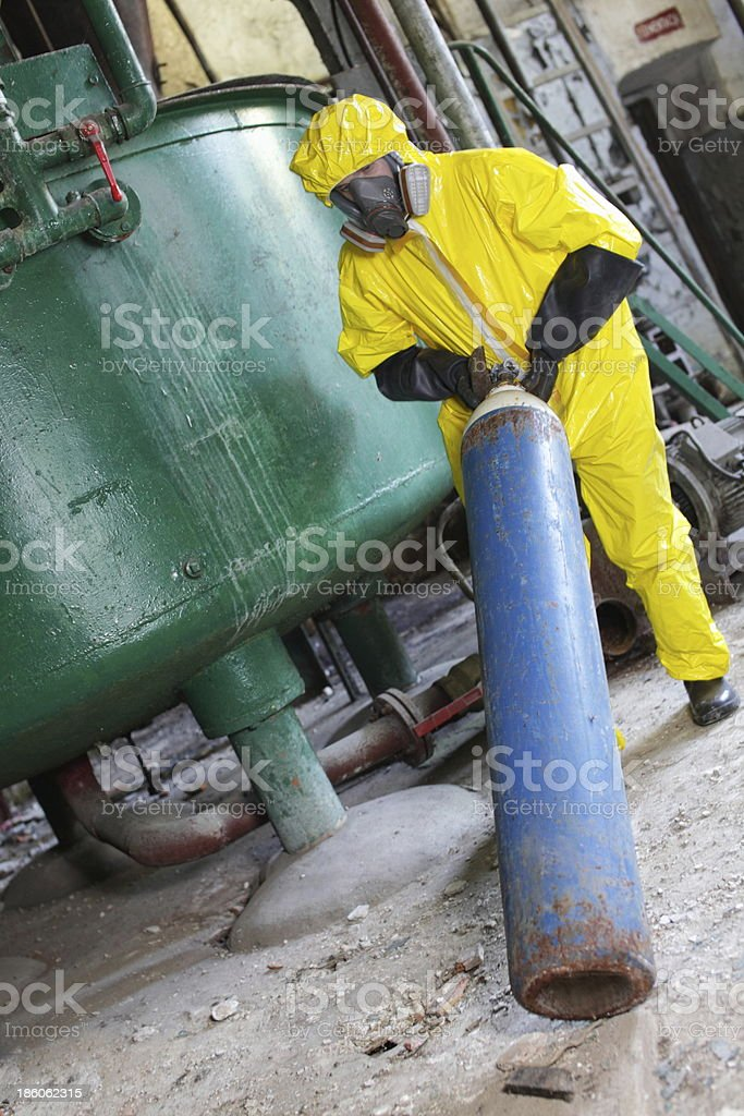 technician in yellow protective uniform dealing with steel cylinder royalty-free stock photo