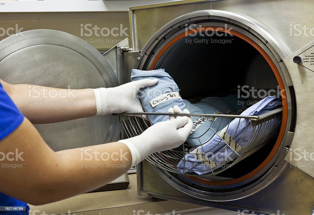 Technician Inserts Surgical Pack in Autoclave for Sterilization. stock photo