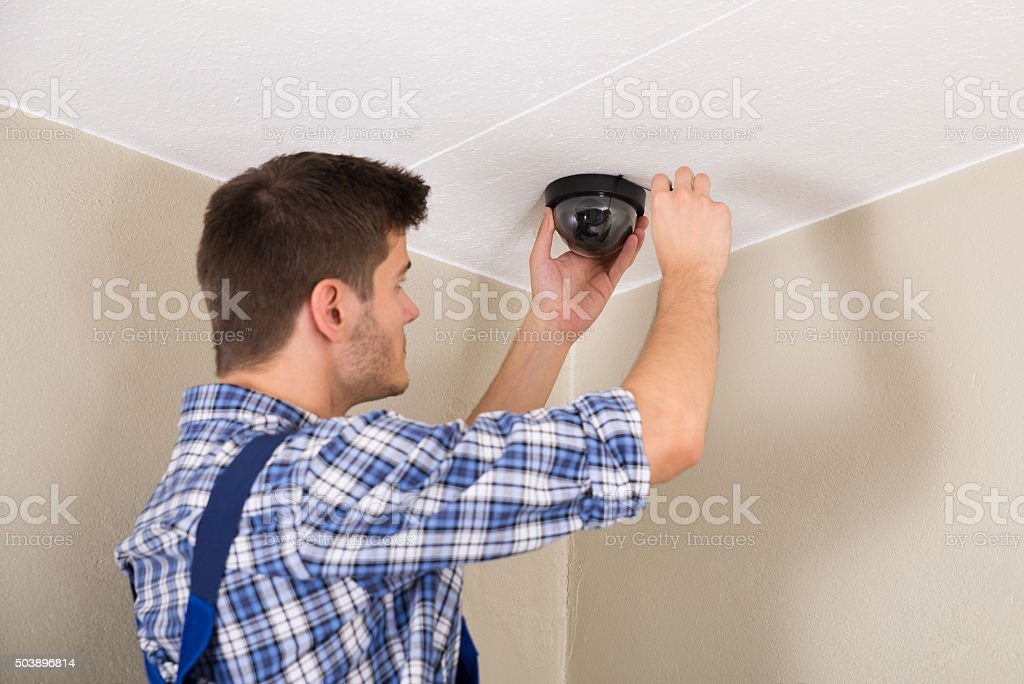 Technician Installing Surveillance Camera stock photo