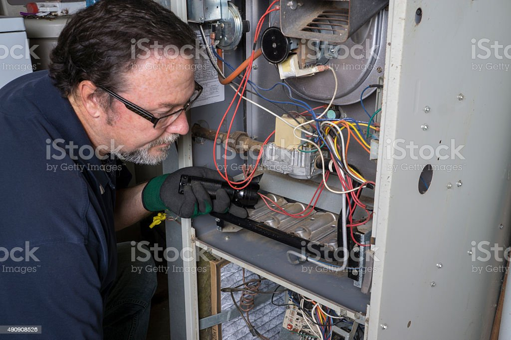 Technician Looking Over A Gas Furnace stock photo
