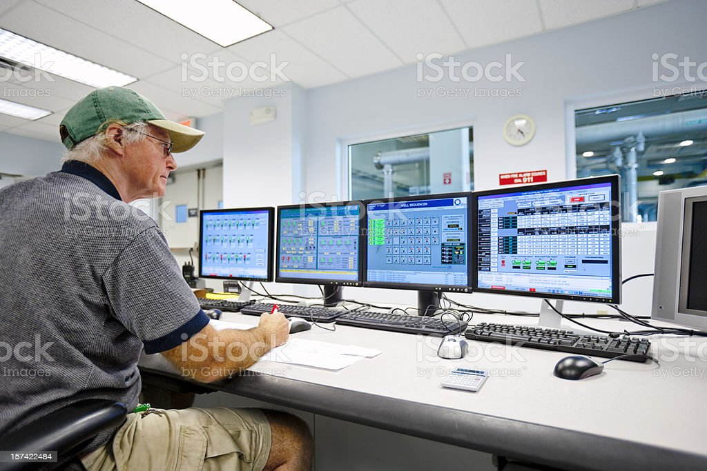 Technician Monitoring in Control Room stock photo