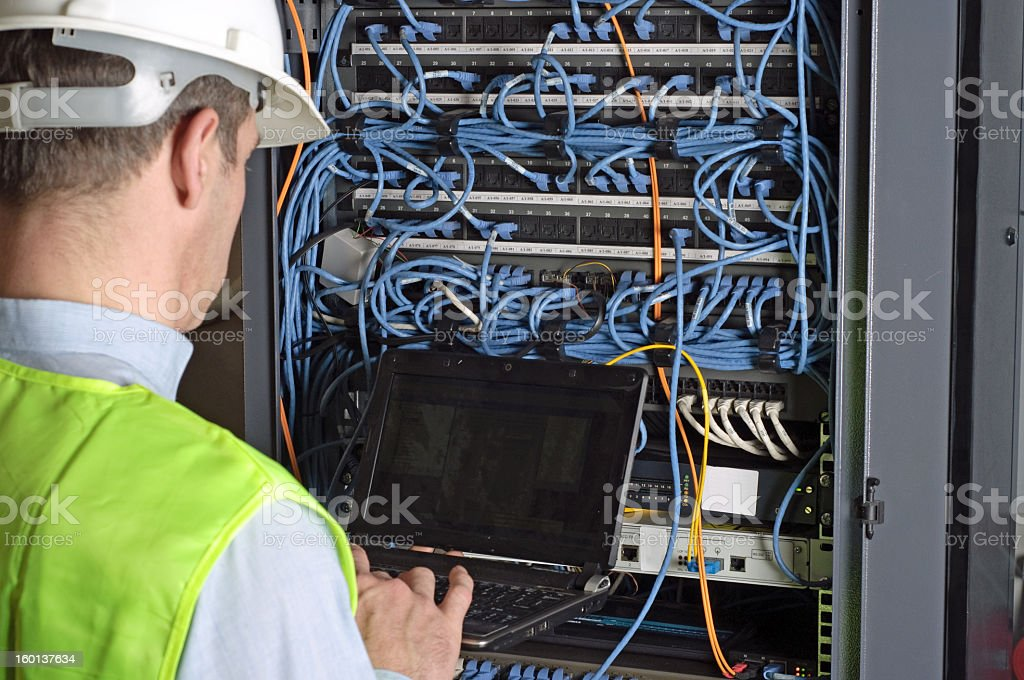 Technician performing work on server using their laptop stock photo