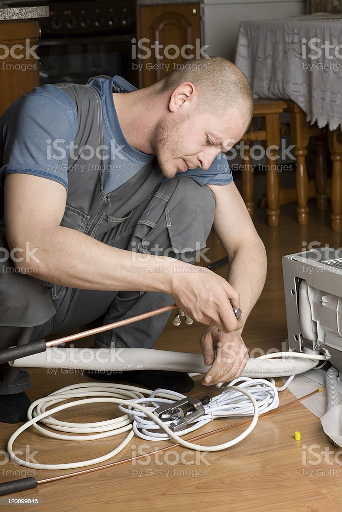 technician prepares a new air conditioner to be installed royalty-free stock photo