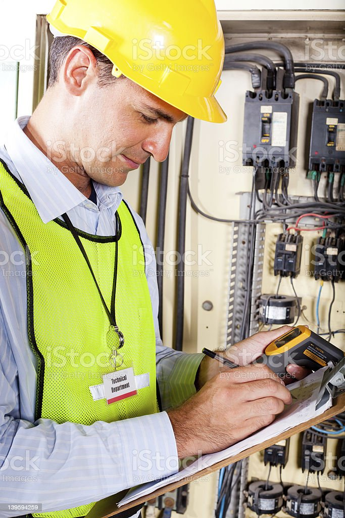 technician recording machine temperature stock photo