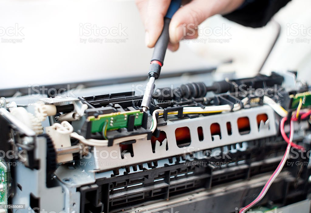Technician repairing a laser printer with tools stock photo