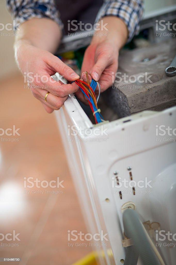 Technician repairing a washing machine, close up stock photo