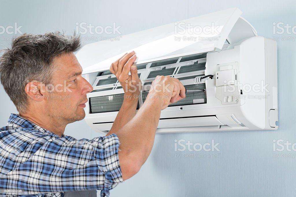 Technician Repairing Air Conditioner stock photo