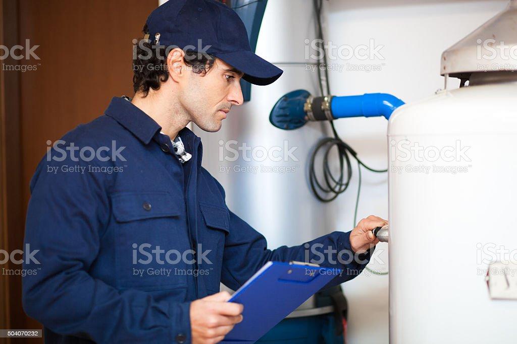 Technician repairing an hot-water heater stock photo