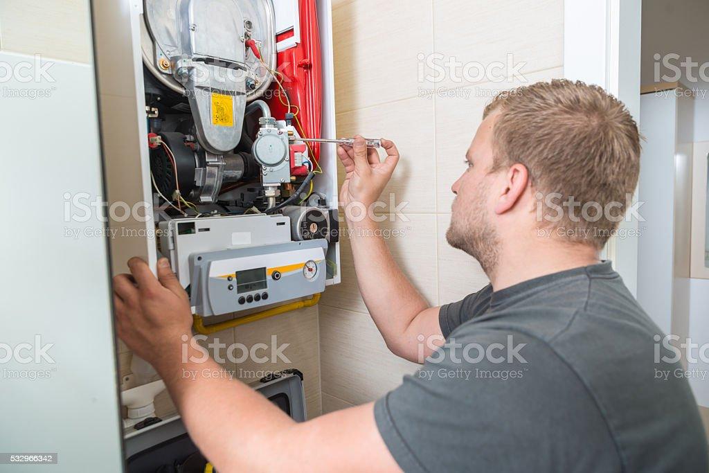 Technician repairing Gas Furnace stock photo