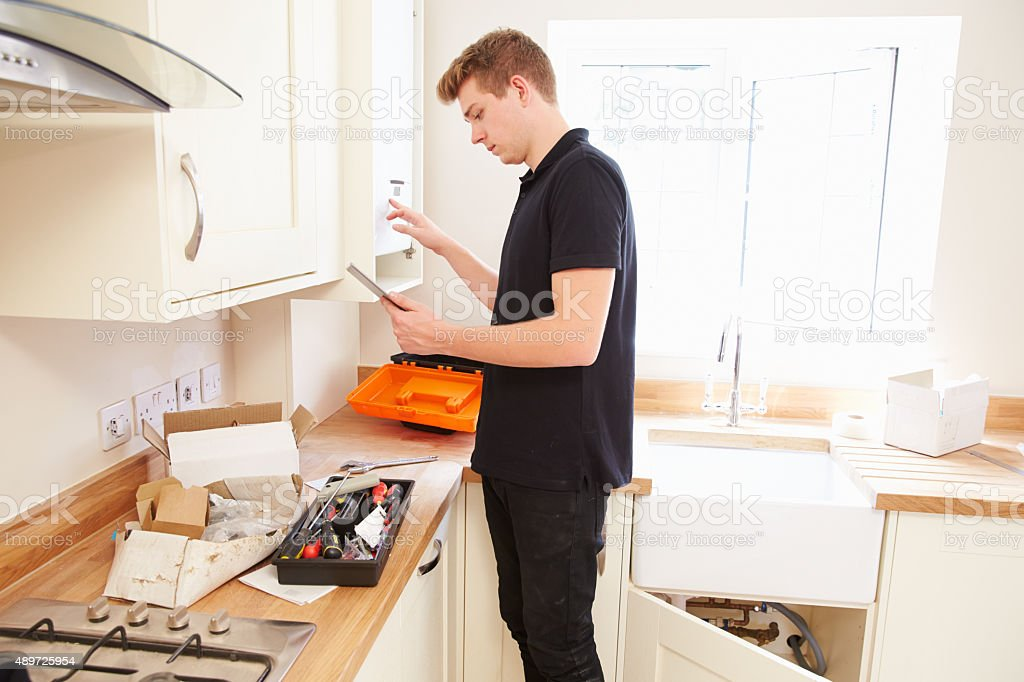 Technician servicing boiler?in kitchen using tablet computer stock photo