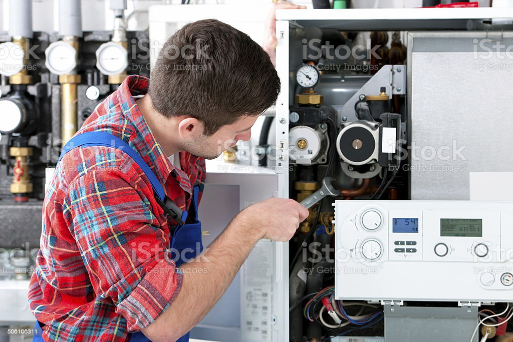 Technician servicing heating boiler royalty-free stock photo