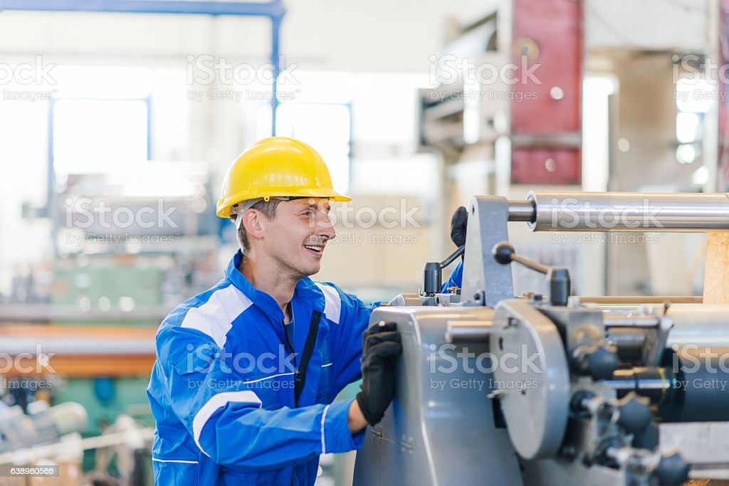 Technician setting up the machine in factory and smiling stock photo