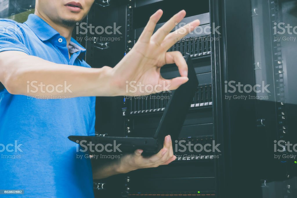 Technician showing OK sign in server cabinet stock photo