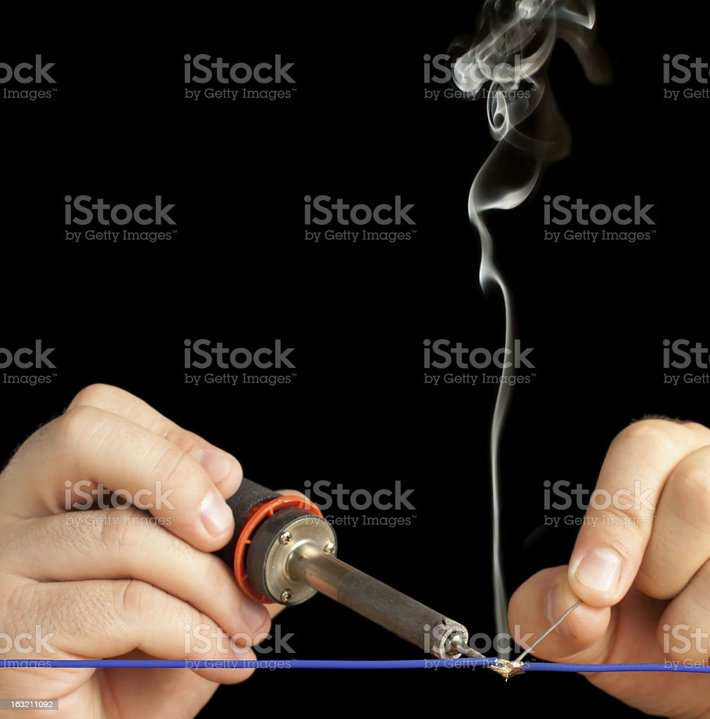 Technician soldering two wires together on a black background. stock photo