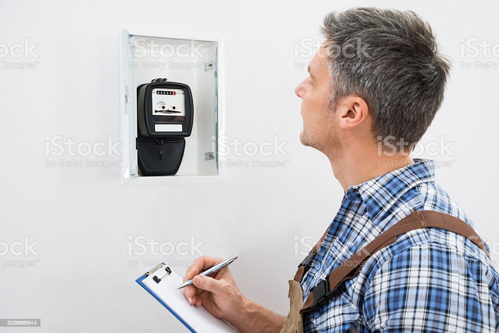 Technician Taking Reading Of Electric Meter stock photo