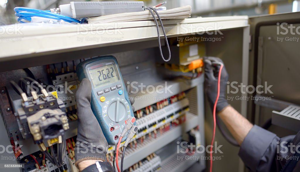 Technician testing a control panel stock photo