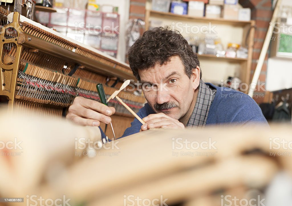 Technician tunes up a grand piano. royalty-free stock photo
