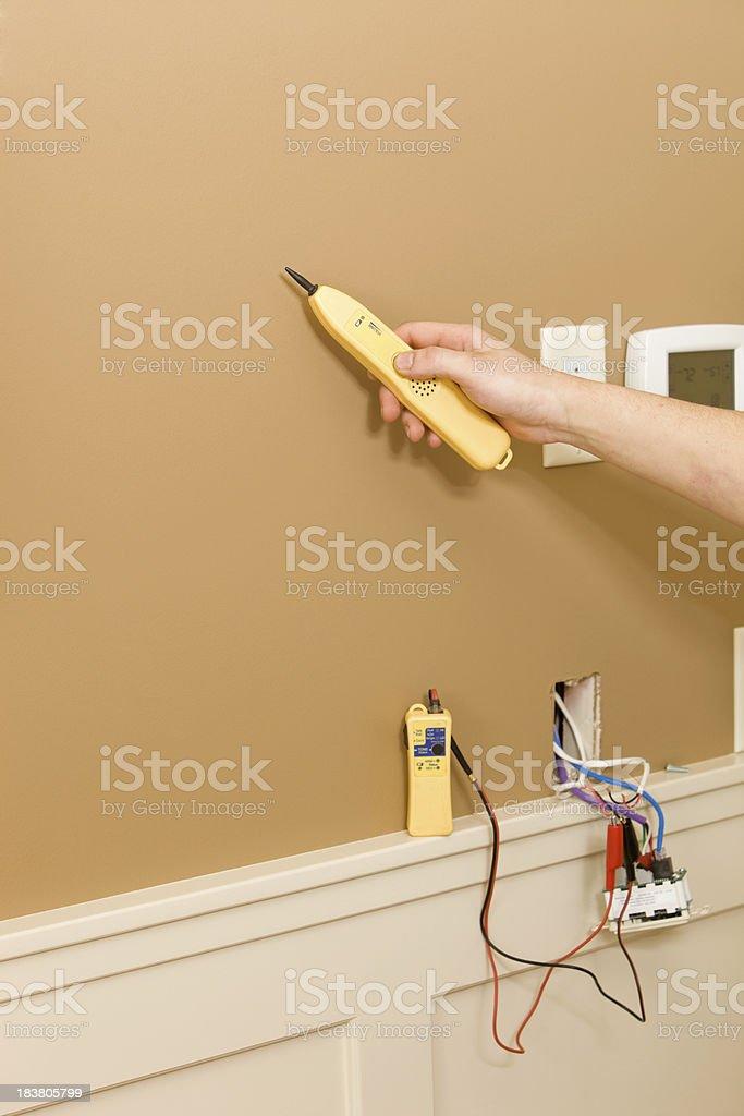 AV Technician Using Tone Probe to Locate Wall Speaker Wires royalty-free stock photo
