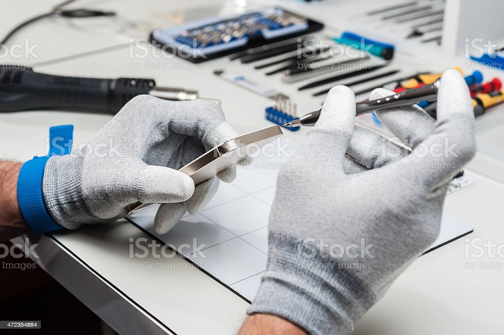 Technician wearing gloves repairing a smartphone stock photo