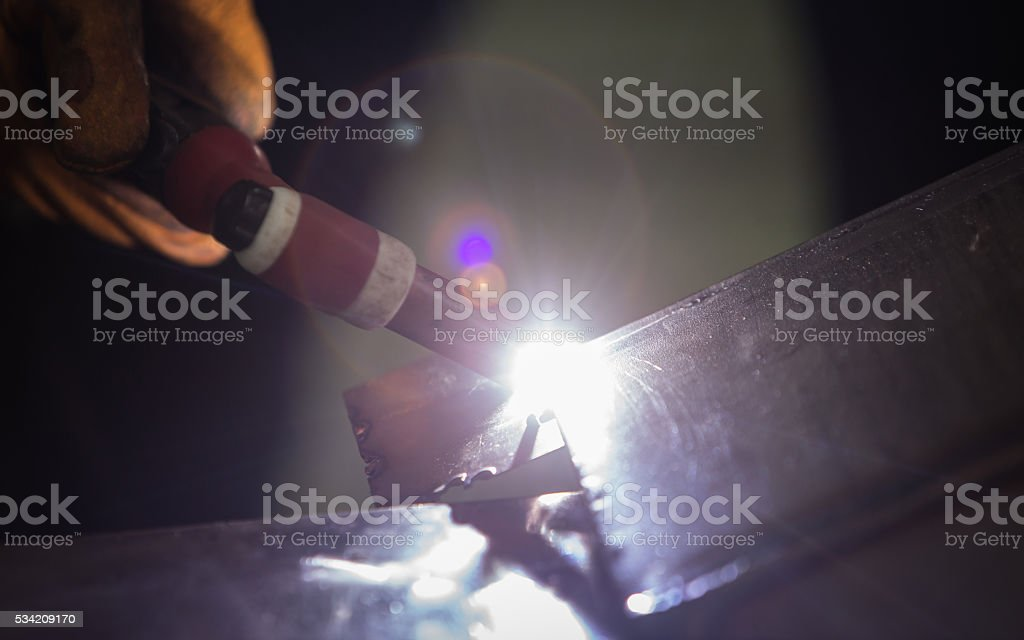 technician welding metal pipe with argon stock photo