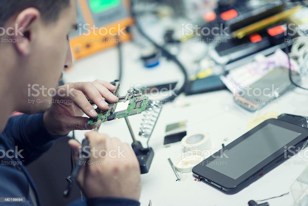 Technician Worker Soldering Elements and Repairing Smart Phone stock photo