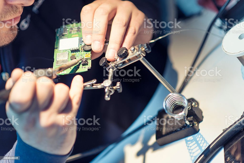 Technician Worker Soldering Elements on Microchip Circuit Board stock photo