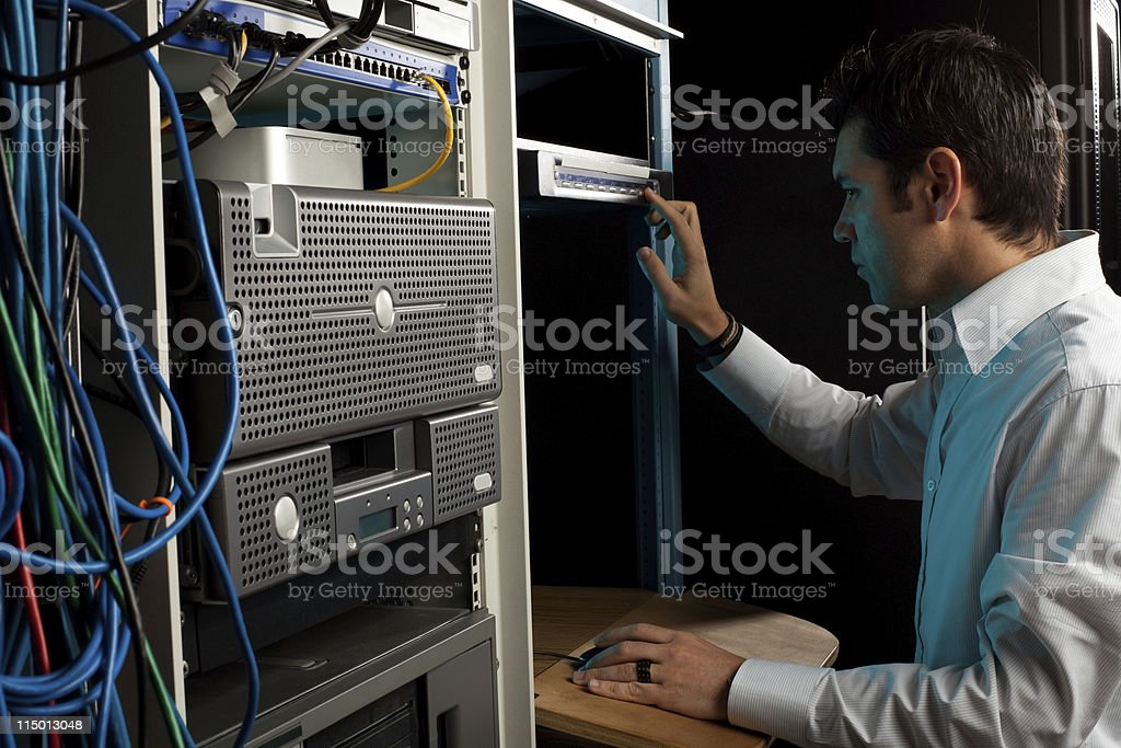 IT Technician Working at Computer Console in Equipment Room stock photo