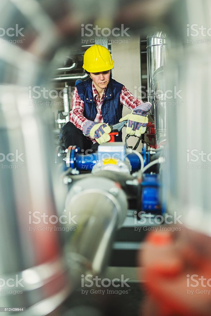 Technician working on valve in factory or utility stock photo