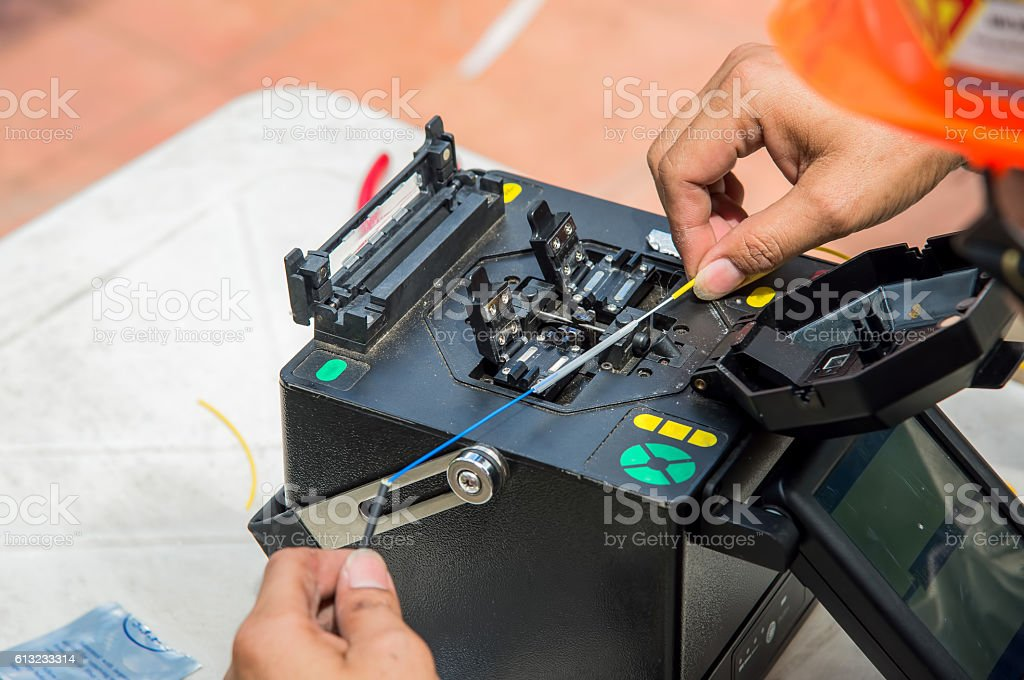 Technicians are cutting and fusion fiber optic cables. stock photo