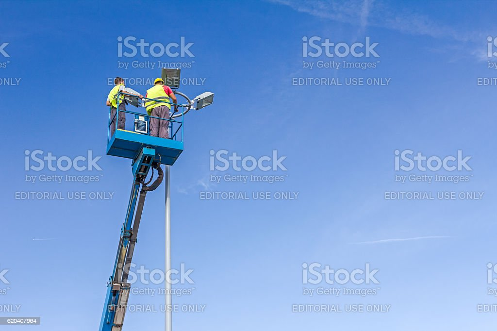 Technicians are working high up on a spotlight tower. stock photo
