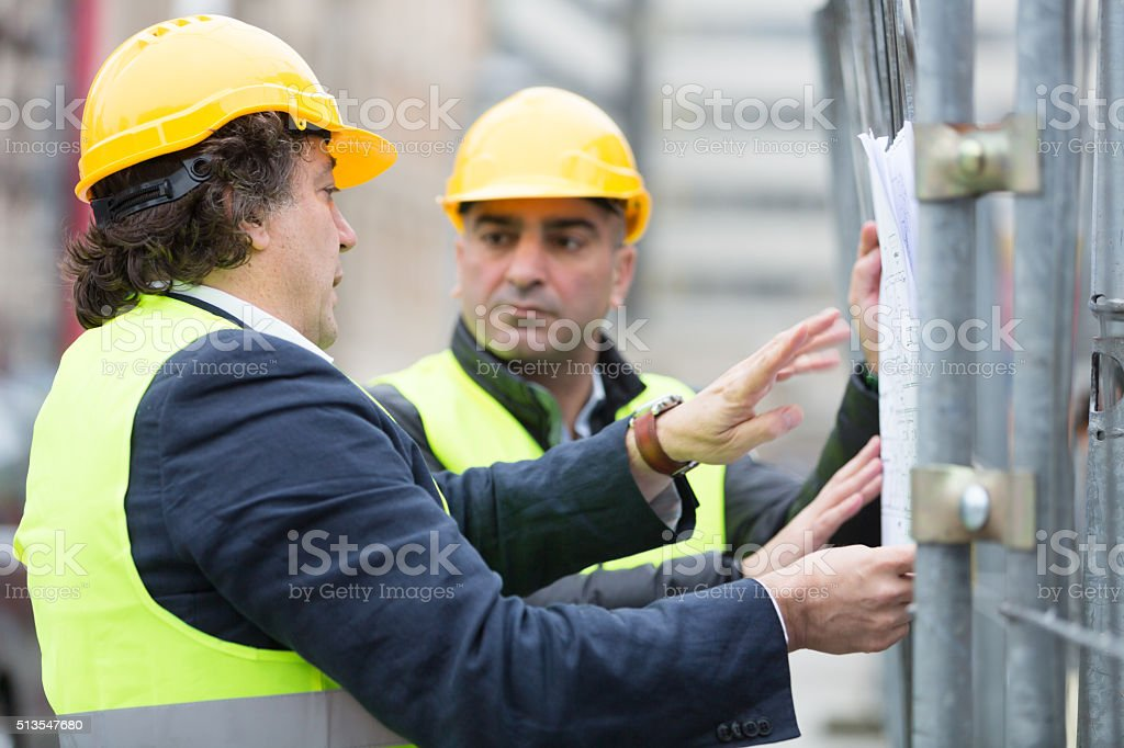 Technicians with office blueprints against scaffolding stock photo