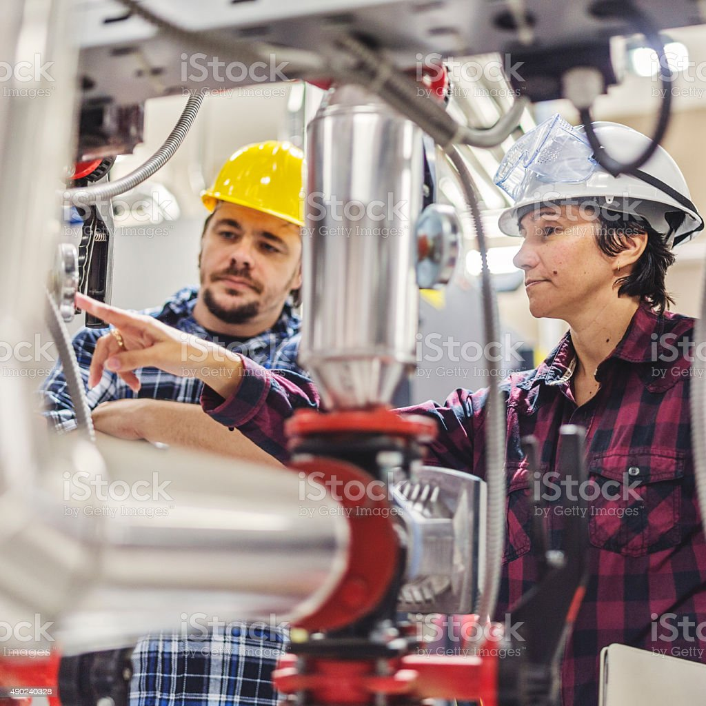 Technicians working on valve in factory or utility stock photo