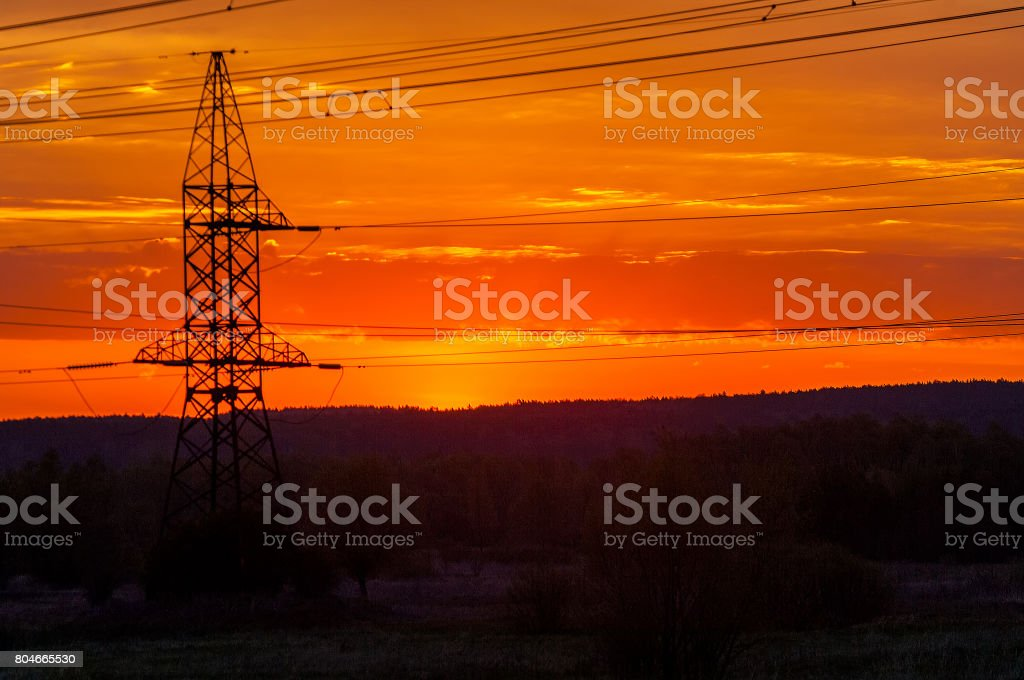 Technogenic landscape, urban. The energy of the pole in the rays of the rising sun. Posts for the transfer of high lead. Steel Electric Pillars stock photo