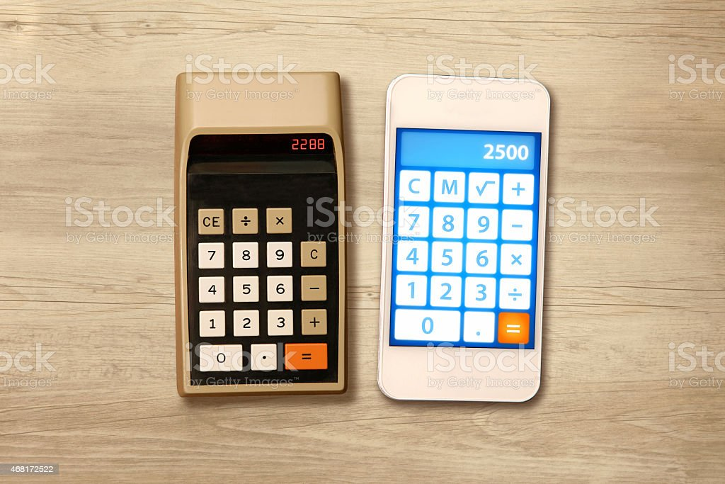 Technology evolution: comparing smartphone with a calculator from the seventies stock photo