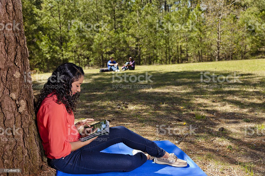 Technology: Female teen uses digital tablet under tree royalty-free stock photo