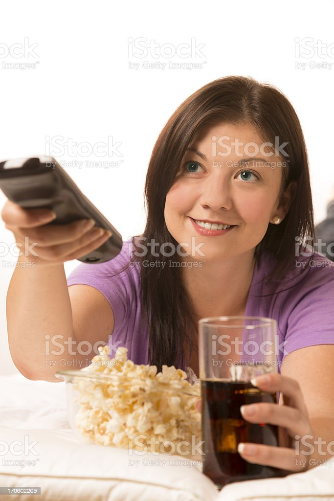 Technology: Female watching TV.  Cold Drink.  Popcorn.  Remote. royalty-free stock photo
