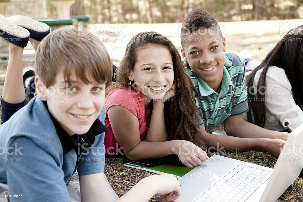 Technology:   Junior high students using laptop to study outside. stock photo
