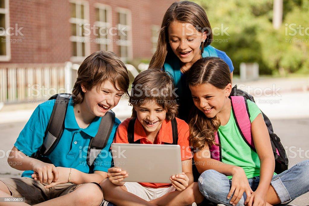 Technology: School children enjoy digital tablet. stock photo