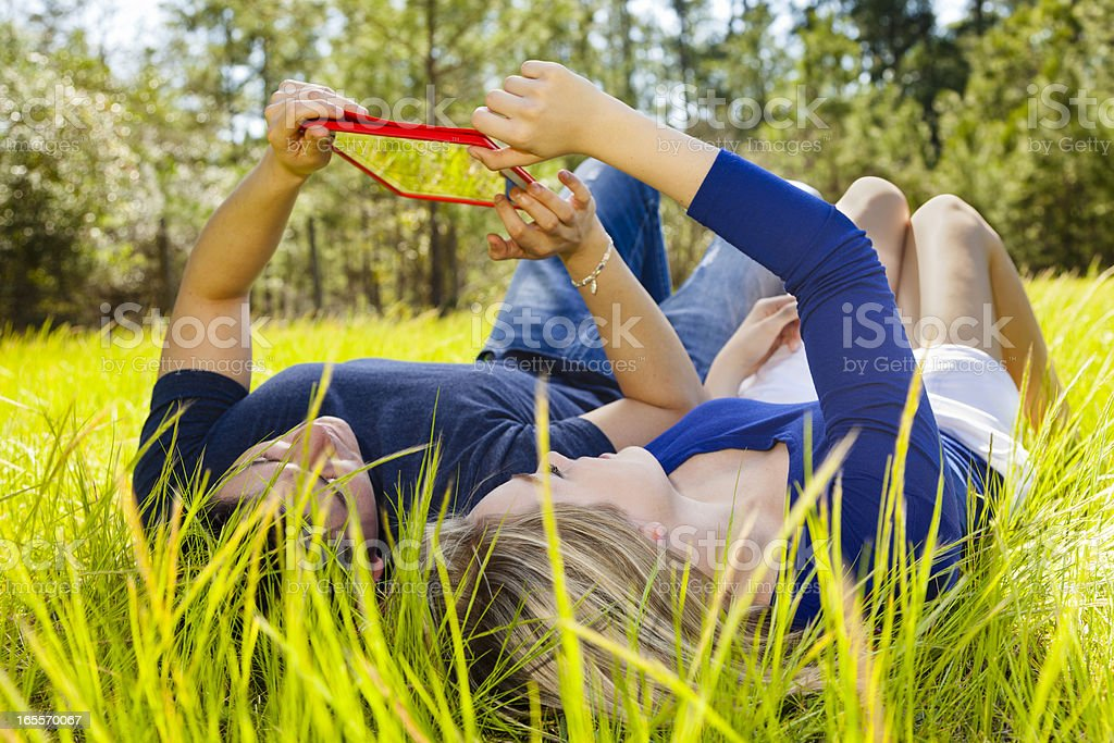 Technology:  Teenagers outside in grassy park using digital tablet. royalty-free stock photo