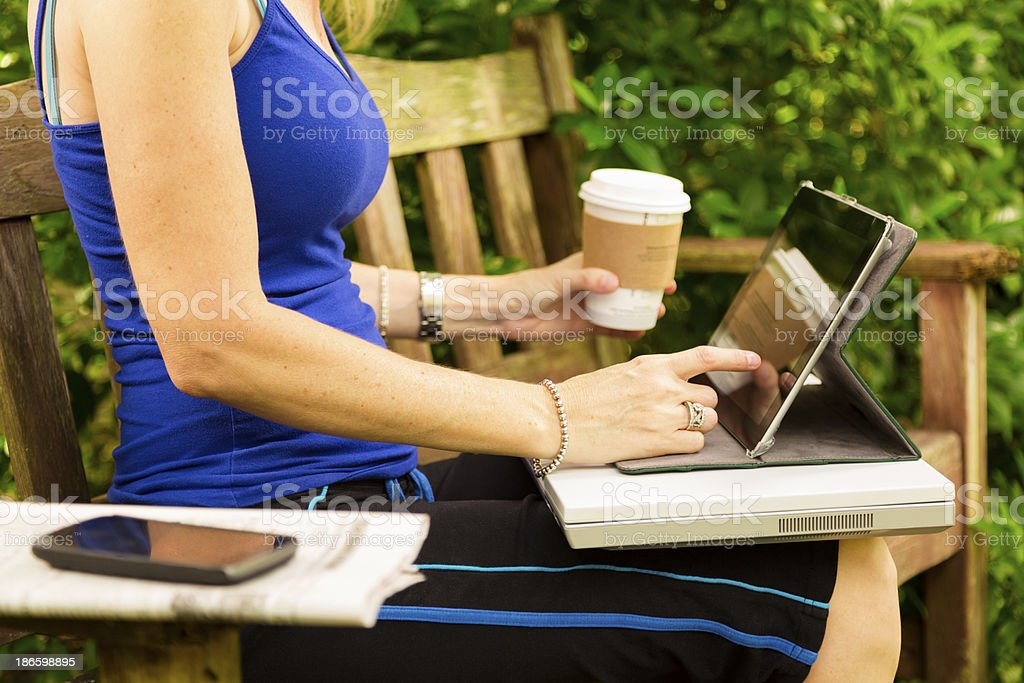 Technology:  Woman uses digital tablet in park. Holding coffee cup. royalty-free stock photo
