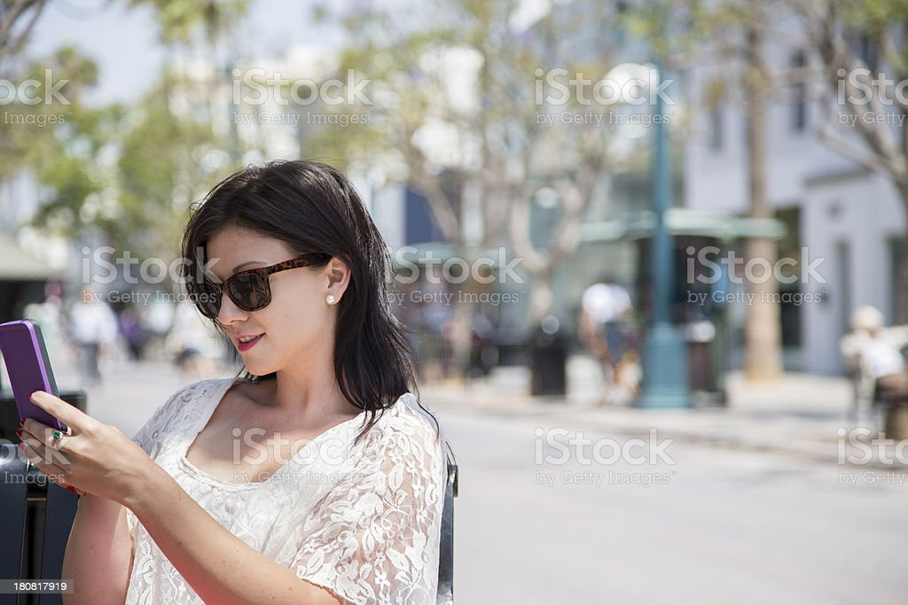 Technology: Young woman outdoor on phone during shopping trip royalty-free stock photo