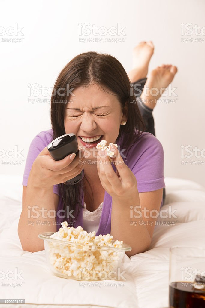 Technoloogy: Female laughing watching TV.  Cold Drink.  Popcorn.  Remote. royalty-free stock photo