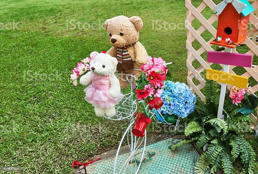 teddy bares are put near colorful faked flowers. stock photo