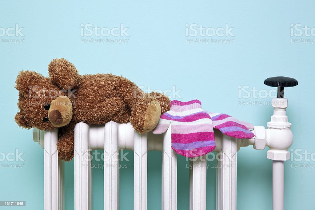 Teddy bear and gloves on an old radiator stock photo